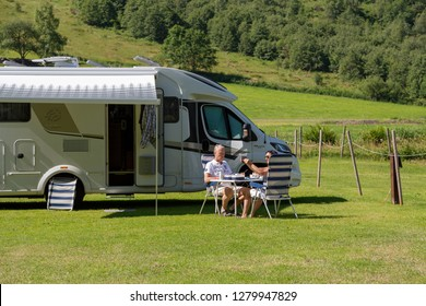 Geiranger, Norway - June 26 2018: A campervan or motorhome in a Geiranger Camping RV park in summertime. Older couple having a lunch in Norwegian fjords.