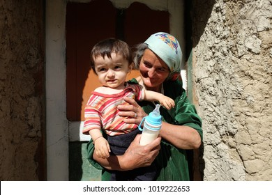 GEISEV, TAJIKISTAN - AUGUST 17, 2017: Grandmother and her child in Geisev Valley, Tajikistan.