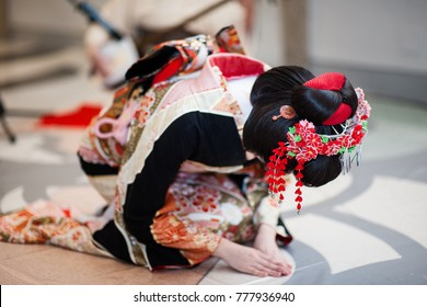 A geisha dancing in kimono, bowing to thanks the guests