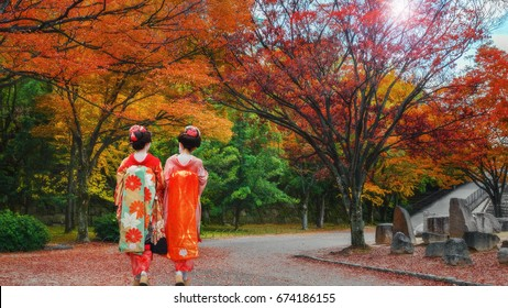 Geisha Girls in a Japanese Garden in Colorful Autumn