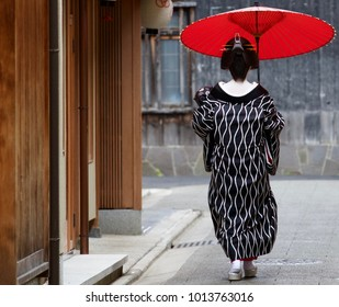 Geisha in Kyoto with a red umbrella walking around in gion among the traditional buildings