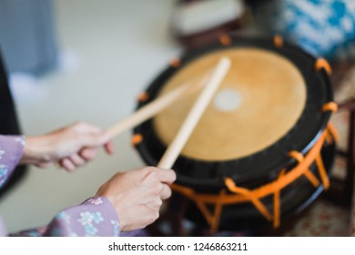 A geisha plays the taiko (traditional drum).