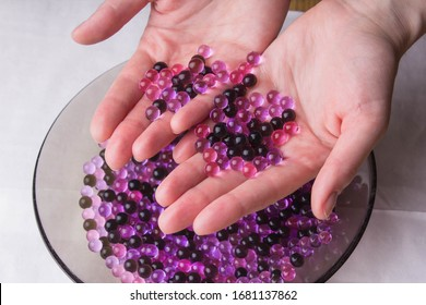 Gel balls in female hands for seedlings or children's game. Hydrogel material for watering or decor flowers. Absorbent for flower pot. Interior design. Top view