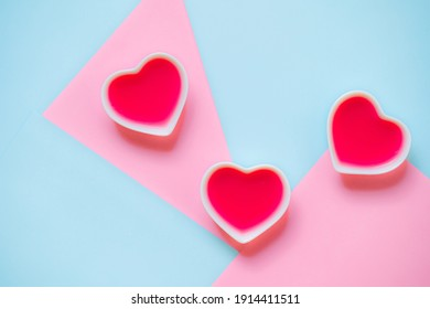Gelatin three red hearts in the white porcelain bowls on the pastel blue and pink geometrical smooth background. Concept of Valentines Day, romance, affair and love. Trendy beautiful food photography.