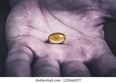 Gelatine Pill In The Middle Of A Dark, Dirty And Used Looking Hand, Top View