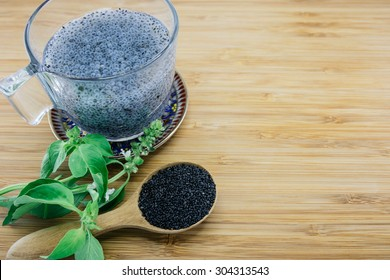 Gelatinous basil seeds in a cup and basil leaves and seed on wood background
