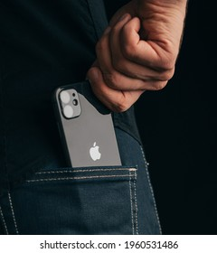 Gelendzhik, Russia, 24 March 2021: The man get out an iPhone 11 out of his pocket. Close-up of the Apple logo and a phone camera.