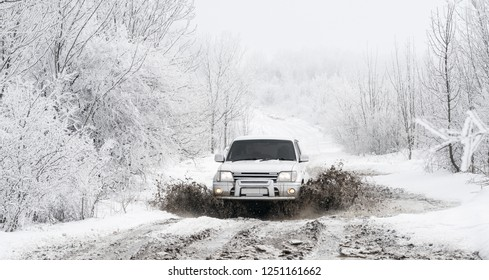 Gelendzhik, Russia, 26 February 2018: Driver man in white jeep Toyota Land Cruiser Prado 90 passes a puddle on the off-road in beautiful snowy winter forest.