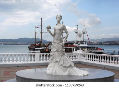 Gelendzhik, Russia. April 27, 2018: The symbol of the city is the Bride. (girl in white wedding dress with bouquet). Monument on embankment. Black Sea and pleasure boat in Gelendzhik, Russia.