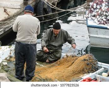 GELIBOLU (GALLIPOLI) , TURKEY-MARCH 29, 2008:  Turkish fishermen work on their nets at the harbor front.