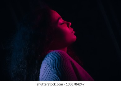 Gelled red and blue light. Biracial teenage girl with eyes closed. Black background