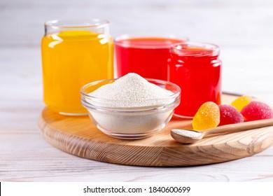 Gelling agents: gelatin, agar-agar or pectin powder with marmalade on wooden cutting board. Gelatine granules used as a gelling agent
