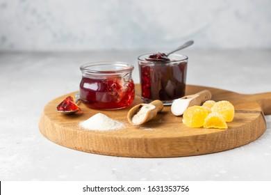 Gelling agents: gelatin powder, agar-agar (vegetarian substitute for gelatin) and pectin powder on wooden cutting board.