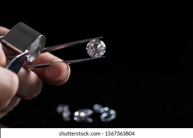 Gem stones. Jeweller checking polished diamond. Carat size diamonds. Diamond trading and dealing. Loose diamond grading. Precious stones.