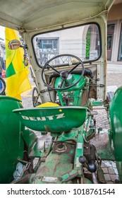 GEMONA, ITALY - NOVEMBER, 2017: cityscape. close up of modern green tractor in autumn market in Gemona Friuli-Venezia Giulia, Italy