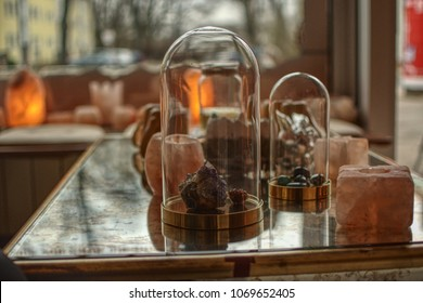Gems amethyst rock crystal in an glass dome and himalaya salt around them on a table