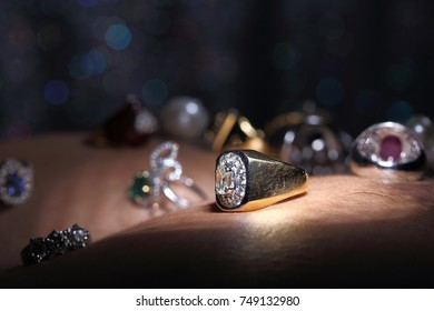Gems, Jewelry, Daimond, Gold Silver, Ruby vavluable Rings presented put on Human Skin over Dark bokeh background with shinny object