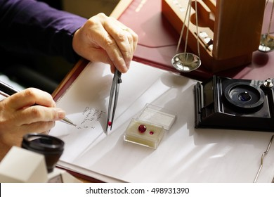 gemstone appraisal  - a gemologist examines a ruby using tweezers and evaluating gemstones - closeup view of gem specialists hands while at work