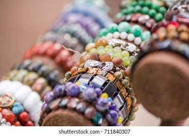 Gemstone bracelets and necklaces in a row. Jewelry made of blue agate crystal, mountain quartz, red coral stones, tiger eye stones. Healing, powerful crystal energy. Esoteric and colorful background.