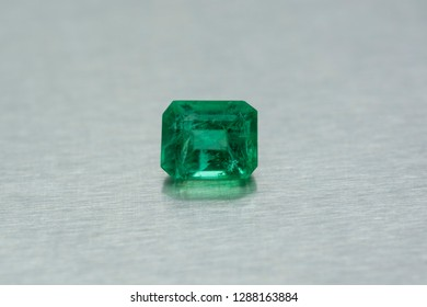 Gemstone carved of emerald on gray metallic background