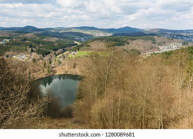 The Gemuendener Maar volcano lake in the Eifel, Germany near Daun in spring seen from the crater rim.