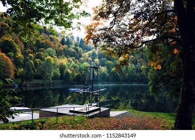 Gemunder Maar volcanic lake in the Eifel near Daun, Germany. Diving tower with a picturesque reflection of autumn trees in the water.