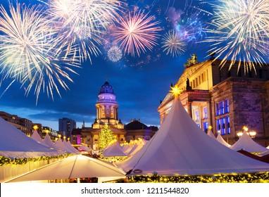 Gendarmenmarkt Christmas market kiosks in Berlin illuminated at night with fireworks, Germany