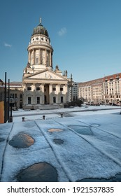 Gendarmenmarkt square in Berlin with French Cathedral, or Franz sischer Dom in German. Picture taken from the steps of Concert Hall on a bright Winter day with blue sky and snow.