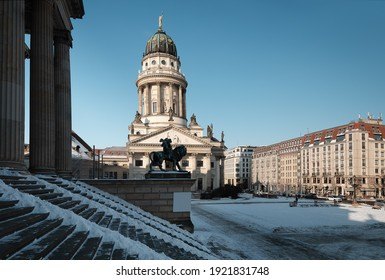 Gendarmenmarkt square in Berlin with French Cathedral, or Franzusischer Dom in German. Picture taken from the steps of Concert Hall on a bright Winter day with blue sky and snow.