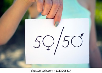 gender differences concept, a piece of paper with a female and a male symbol in a woman's hand