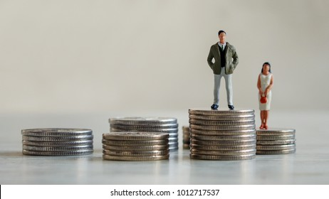 Gender discrimination concept. A miniature man  and miniature woman standing on the coin.