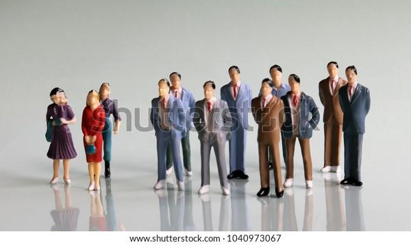 Gender discrimination concept in society. Threewomenandabunchofminiaturemen.