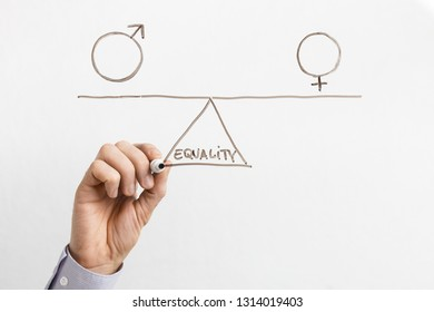 Gender equality between men and women. Man drawing female and male symbols on seesaw on glass board, empty space