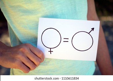 gender equality concept, a piece of paper with a female and a male symbol in a woman's hand