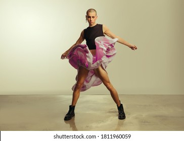 Gender fluid young man in crop top and skirt dancing in studio. Gay man dancing in flowy skirt