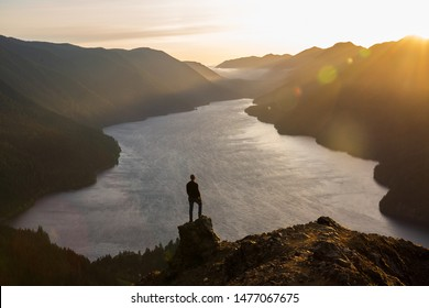 gender neutral hiker silhouetted against mountain backdrop overlooking lake at sunset