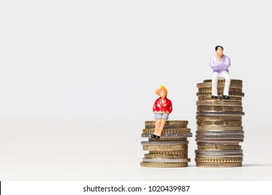 Gender pay equality concept. man and woman on a stack of coins.
