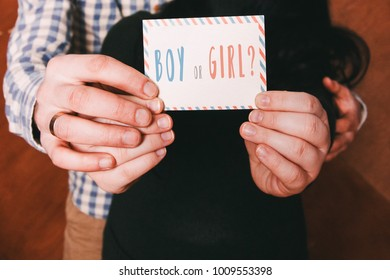 """Gender reveal party, husband and wife are holding postcard that says: """"Boy or girl?"""". Party invitation, pink or blue, male or female, future parents, man's and woman's hands, little postcard"""