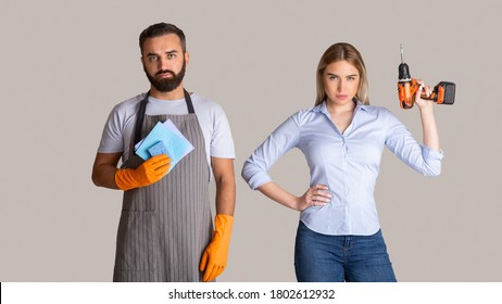 Gender stereotypes and non female profession. Serious man in apron and rubber gloves holding sponges and woman holding a drill on gray background, studio shot