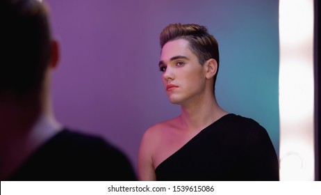 Genderqueer with half-face makeup looking in mirror, non-binary identity concept
