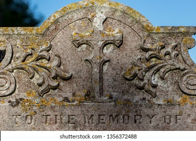 Genealogy and ancestry. Old religious graveyard headstone to the memory of ancient ancestor relatives. English cemetery close-up of a stone memorial with Christian cross..