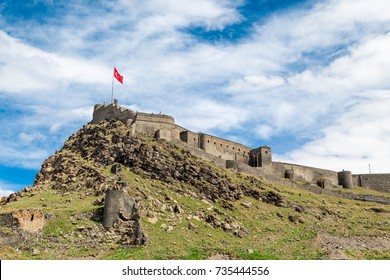 General bottom view of historical famous Kars Castle on meadow hill, Kars, Eastern Anatolia Region Turkey on cloudy sky background.