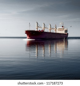 General cargo ship with cranes sailing in a still water. Dramatic sky, dark clouds before the storm. Freight transportation, nautical vessel, global communications, industry, carrying, logistics