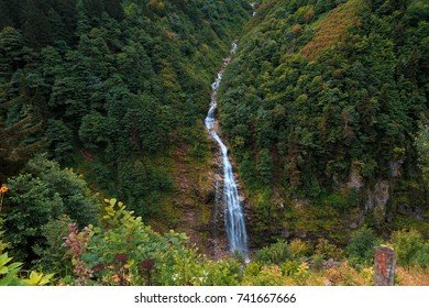 General landscape view of waterfall on a mountain in Ayder Plateau, Rize. Waterfall is flowing between trees.