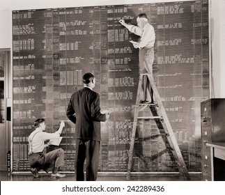 General Motors managers at a large control board, which resembles a spreadsheet, keep check on flow of materials needed for the wartime production. 1941.