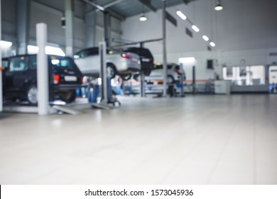 General plan of the car service station. The posts and lifts with the cars in blur, the background image of the service center.