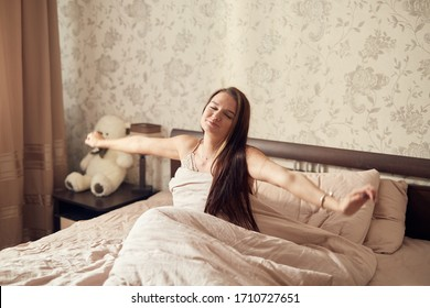 general plan a girl with long dark hair sits on a bed in a nightgown boudoir stretches after sleeping in a bedroom in the morning