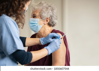 General practitioner vaccinating old patient in clinic with copy space. Doctor giving injection to senior woman at hospital. Nurse holding syringe before make Covid-19 or coronavirus vaccine. - Shutterstock ID 1850607544
