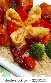 General Tso, fried rice, crab rangoon in kitchen or restaurant setting.