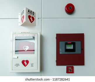 General view of a life saving defibrillator. Portable automated external defibrillator (AED) and fire alarm system mounted on the wall in public restroom at airport.